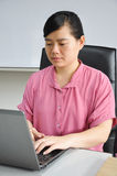 An asian woman works with computer Stock Photography
