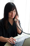 An asian woman works with computer with telephone Royalty Free Stock Photo