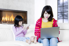 Asian woman works at home with daughter Stock Photos