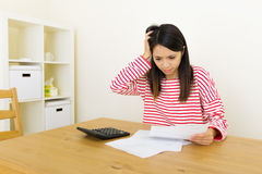 Asian woman worries about the expenditure. At home Stock Images