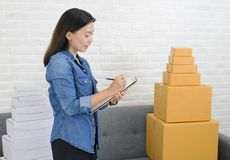 Asian women write note of orders with box at home business concept. Asian woman write note of orders with box at home business concept stock photo
