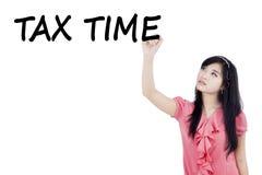 Asian woman writes Tax Time Royalty Free Stock Photo