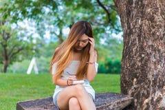 Asian woman writing on book at a garden or park Royalty Free Stock Photos