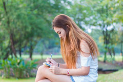 Asian woman writing on book at a garden or park Royalty Free Stock Images