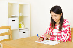 Asian woman writing on notebook Stock Photos