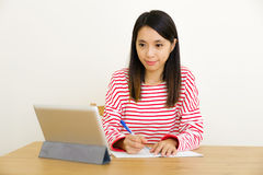 Asian woman writing notes through digital tablet Royalty Free Stock Image
