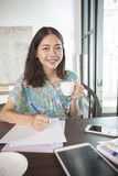 Asian woman writing pen on white paper and hot beverage cup in h Royalty Free Stock Photos