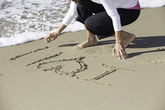 Asian woman writing on sand with white crashing wave Stock Image