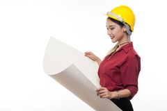 Asian woman with yellow safety helmet. Young Asian woman architect with red shirt and yellow safety helmet smiling while reading blueprints. Industrial Royalty Free Stock Images