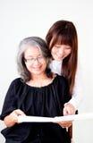 Asian women. Happy senior asian women enjoy reading with her granddaughter Royalty Free Stock Image