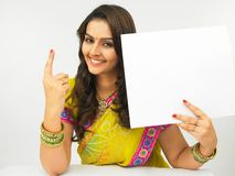 Asian women with a balnk placard. Asian women of indian origin showing the index finger royalty free stock image