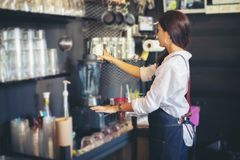 Asian women Barista smiling and using coffee machine in coffee s royalty free stock image
