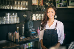 Asian women Barista smiling and using coffee machine in coffee s. Asian woman Barista smiling and using coffee machine in coffee shop counter - Working woman Royalty Free Stock Photography