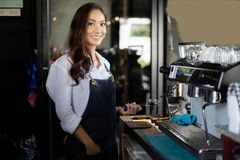 Asian women Barista smiling and using coffee machine in coffee s stock photos