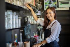 Asian women Barista smiling and using coffee machine in coffee s stock photo