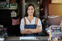 Asian women Barista smiling and using coffee machine in coffee shop counter - Working woman small business owner food and drink