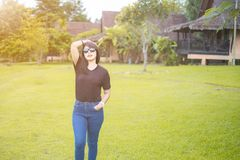 Asian Women, Beautiful. wearing sunglasses. Wear a casual dress black t-shirt with Blue jeans. Standing poses with lift arm up. stock photo