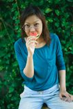 Asian Women biting Slice Of Watermelon. With green background royalty free stock photos