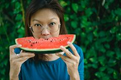 Asian Women biting Slice Of Watermelon. With green background stock photo