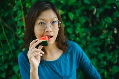Asian Women biting Slice Of Watermelon. With green background stock photography