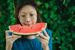 Asian Women biting Slice Of Watermelon. With green background stock image