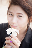 Asian women black shirt. Holding white flower. Stock Image