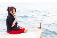 Asian women black shirt. Sitting on the sidewalk. Royalty Free Stock Photos