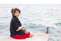 Asian women black shirt. Sitting on the sidewalk. Stock Photos