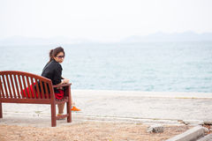 Asian women black shirt. Sitting on wooden bench. Royalty Free Stock Image