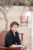 Asian women black shirt. Sitting on wooden bench. Royalty Free Stock Photos