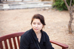 Asian women black shirt. Sitting on wooden bench. Stock Photography
