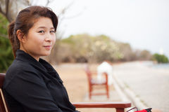 Asian women black shirt. Sitting on wooden bench. Stock Image