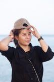 Asian women black shirt. She was wearing a hat Stock Image