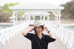 Asian women black shirt. She is wearing a hat Stock Image