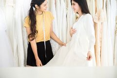 Asian women bride trying on wedding dress,Woman designer making adjustment with measuring tape stock images