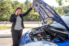 Asian women calling for assistance after breaking down car engin Royalty Free Stock Images
