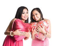 Asian women celebrating valentine. Two beautiful asian women carrying heart-shaped balloons celebrating valentine day Stock Images