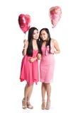 Asian women celebrating valentine day. Two beautiful asian women carrying heart-shaped balloons celebrating valentine day Royalty Free Stock Images