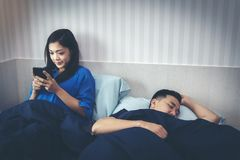 An Asian woman is chatting on a smartphone with her boyfriend, w royalty free stock photography