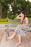 Asian women distracted on bench faced right Royalty Free Stock Photography