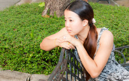 Asian women distracted in park. Asian women distracted on bench in park Stock Image