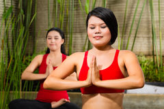 Asian women doing yoga in tropical setting Stock Image