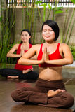 Asian women doing yoga in tropical setting Stock Photos