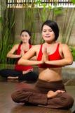 Asian women doing yoga in tropical setting Stock Photos
