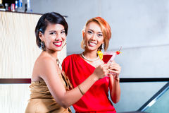 Asian women drinking cocktails in bar. Asian women drinking cocktails in fancy bar stock photos