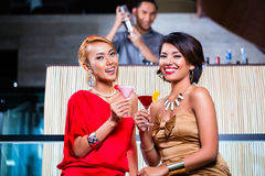 Asian women drinking cocktails in bar. Asian women drinking cocktails in fancy bar Royalty Free Stock Photography