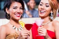 Asian women drinking cocktails in bar. Asian women drinking cocktails in fancy bar Royalty Free Stock Photos