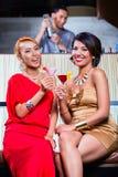 Asian women drinking cocktails in bar. Asian women drinking cocktails in fancy bar Stock Image