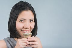Asian women drinking sake in Hands. Beautiful Asian woman with a cup of sake in hand. To drink happily on gray Background Royalty Free Stock Image