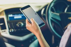 Asian women are driving cars and using a smartphone on the road. stock photography
